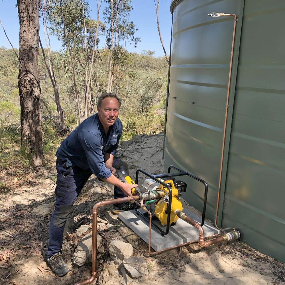 Licensed plumber and professional firefighter, Anthony Walsh, installing a pump on a bush fire sprinkler protection system.
